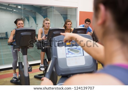 Instructor motivates happy people at spinning class at gym - stock photo