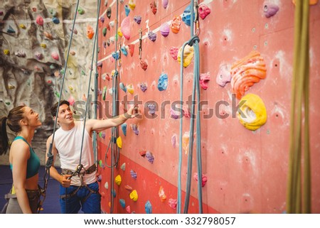 Instructor showing woman rock climbing wall at the gym - stock photo