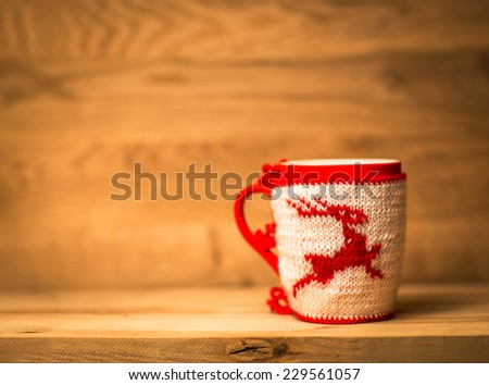 insulated wool cloth mug with embroidered deer on the wooden table - stock photo
