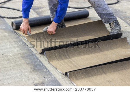 Insulation worker cutting insulation bitumen material rolls, insulation tar material over concrete slabs to keep water out.  - stock photo