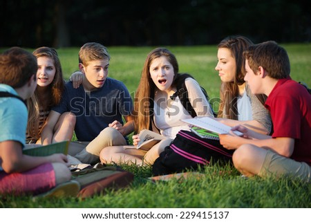 Insulted young female student with friends studying outdoors - stock photo