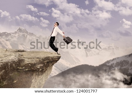 Insurance agent scared because he is standing on top of high mountain - stock photo