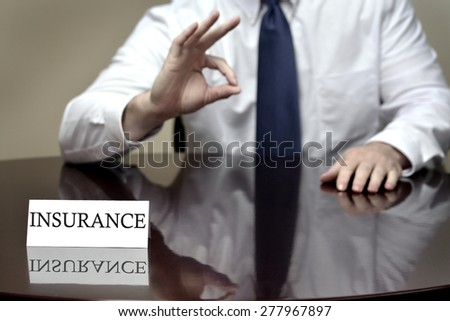 Insurance agent sitting at desk holding hand with OK sign for good coverage - stock photo