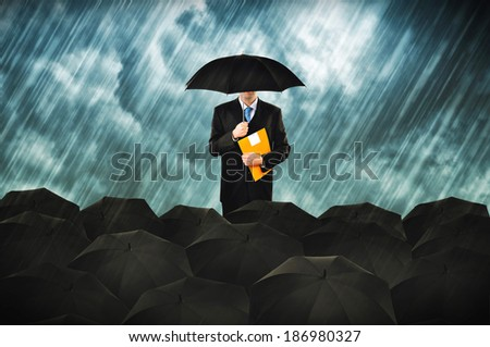 Insurance agents in heavy rain. Businessmen with umbrella gathering for protest. - stock photo