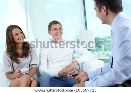 Insurance consultant or financial adviser having a friendly talk with a young couple - stock photo