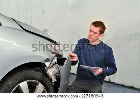 Insurance expert examining car damage. - stock photo