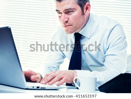 Insurance investigator on his laptop, following a lead on a fraudulent claim. Business, insurance, corporate and career concept - stock photo