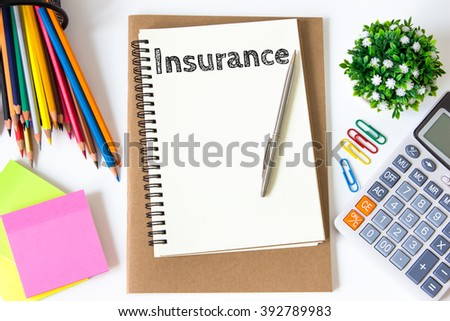 insurance text message on white paper and office supplies, pen, paper note, on white desk , copy space / business concept / view from above, top view - stock photo