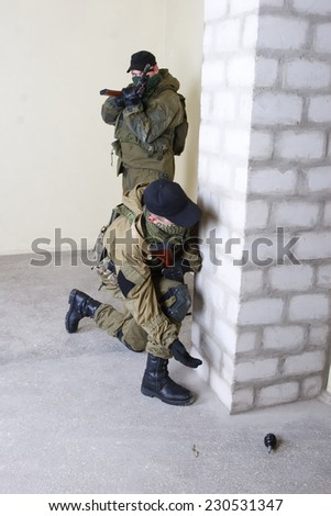 insurgents with AK 47 throws a grenade inside the building - stock photo
