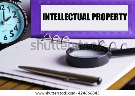Intelectual Property - Purple Office Folder on Background of Working Table with Magnifying glass,  a pen and clock - business and finance concept - stock photo