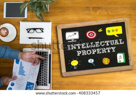 INTELLECTUAL PROPERTY Businessman working at office desk and using computer and objects, coffee, top view, - stock photo