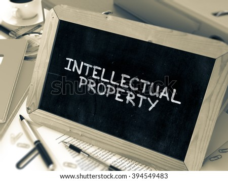 Intellectual Property Handwritten on Chalkboard. Composition with Small Chalkboard on Background of Working Table with Ring Binders, Office Supplies, Reports. Blurred, Toned Image. 3D Render. - stock photo