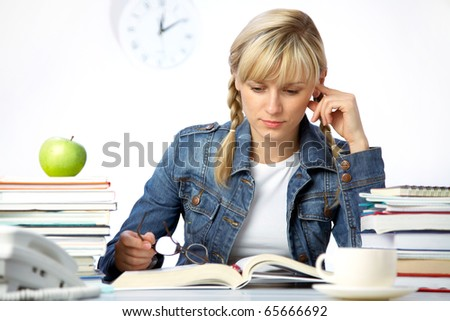 Intelligence girl student reads books in classroom - stock photo