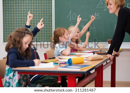 Intelligent class of young boys and girls all raising their hands to show they know the answer to a question asked by a smiling attractive young female teacher - stock photo