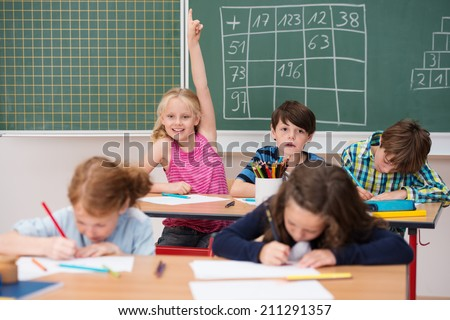 Intelligent enthusiastic little girl in class holding up her hand with a happy smile to attract attention and answer a question - stock photo