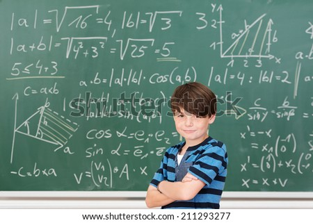 Intelligent kid smiling while posing with folded arms in front of a green blackboard full of mathematical formulas and solved exercises, in the classroom of an elementary school - stock photo