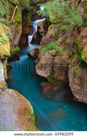 Intense blue glacial melt water rushing through the narrow canyon of Avalanche Gorge, Glacier National Park. - stock photo