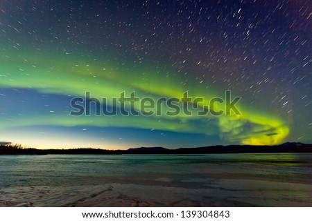 Intense Northern Lights or Aurora borealis or polar lights and morning dawn on night sky over icy landscape of frozen Lake Laberge Yukon Territory Canada - stock photo