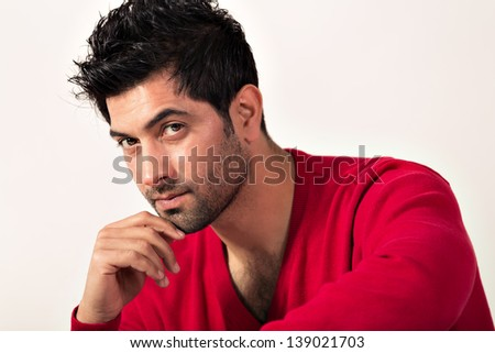 Intense portrait of a man with his hand under the chin, close up of a handsome Indian man - stock photo