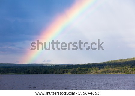 Intense Rainbow over surface of northern boreal forest taiga lake, northern British Columbia, Canada - stock photo