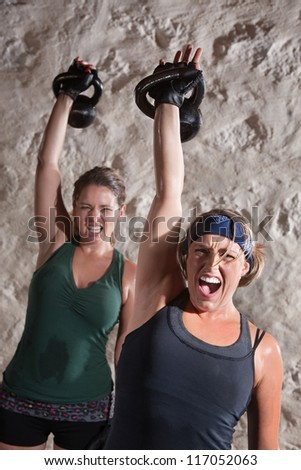 Intense women shout as they push kettle bell weights up - stock photo