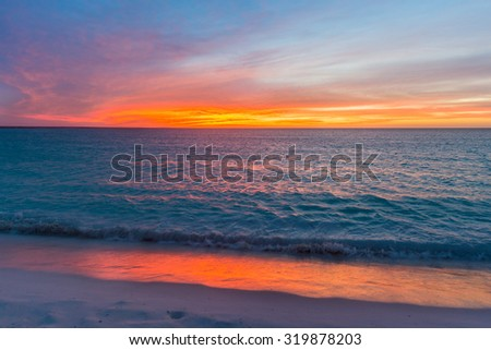 Intensely colored skies at sunset at the Tortuga Island in the Caribbean sea of Venezuela.  - stock photo