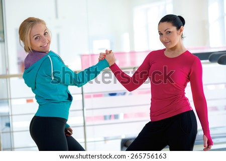 Intensive female training together. Couple of young and beautiful women are having workout in a gym. Perfect shape. Sportsmen. Good workout in a gym. Communication and sport - stock photo