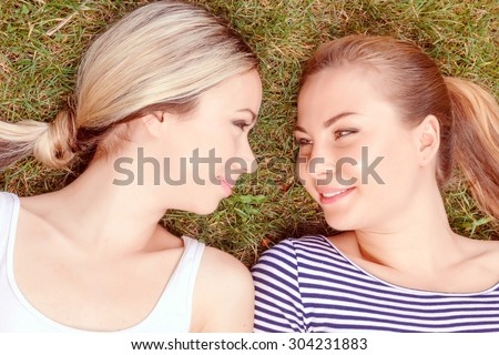 Intent glance. Top view of two young beautiful lesbian women lying on grass and looking at each other. - stock photo