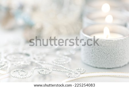 Intentional selective focus to create soft details as holiday background. Christmas candles with ribbon and glittery snowflake ornament.  - stock photo