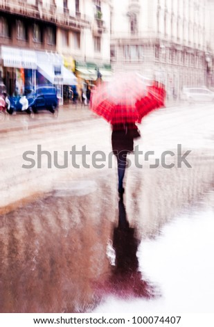 Intentionally motion blurred abstract image of a woman walking with a red umbrella under the rain. Shot in Milan, Italy - stock photo