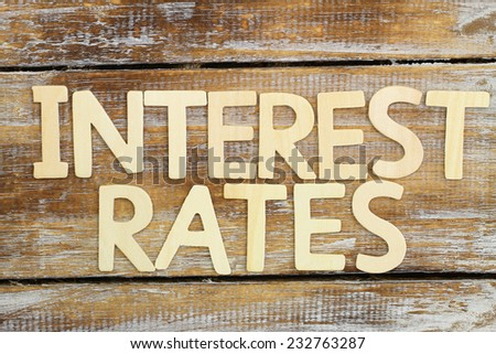 Interest rates written with wooden letters on rustic wooden surface  - stock photo
