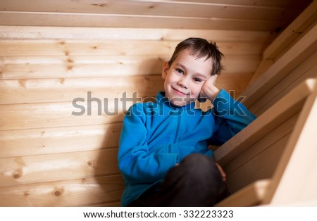 interested listener. boy sits on a steep wooden stairs, smiles and listens with interest - stock photo