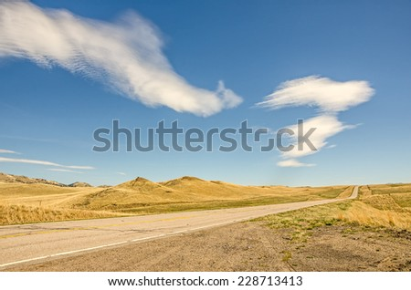 Interesting clouds over an open road with no traffic in Big Sky Country - stock photo