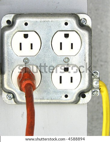 Interesting detail of quad outlet with one orange cord going out and one yellow cord going in. The orange cord comes out directly towards the viewer, the yellow cord is on the right side of the box - stock photo
