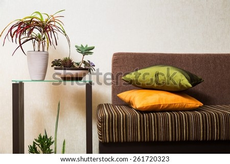 Interior. Bright cushion on a sofa, and orange chrysanthemums on a side table. - stock photo