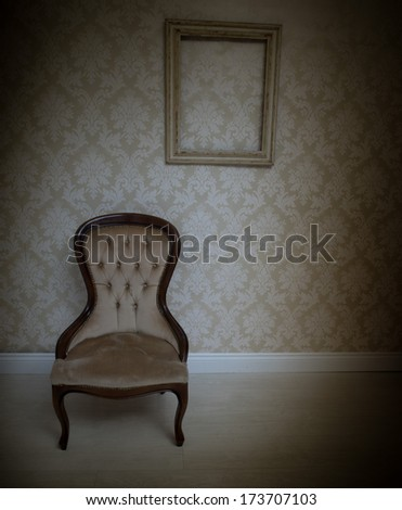 Interior decor background with a vintage upholstered chair standing below an empty wooden picture frame on a wallpapered wall with a retro arabesque pattern in beige with heavy corner vignetting - stock photo
