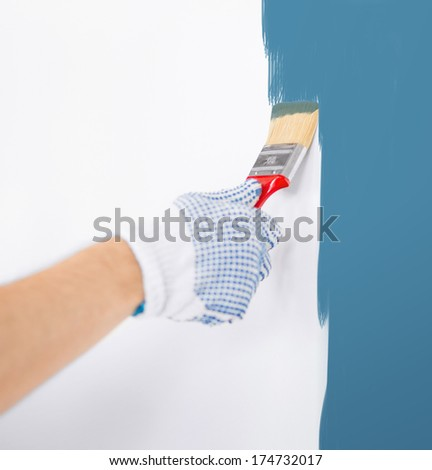 interior design and home renovation concept - man hand coloring white wall with paintbrush - stock photo