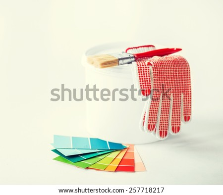 interior design and home renovation concept - paintbrush, paint pot, gloves and pantone samplers - stock photo