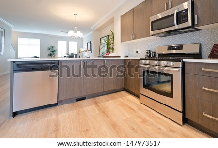 Interior design of a luxury modern kitchen with the living room at the back. - stock photo