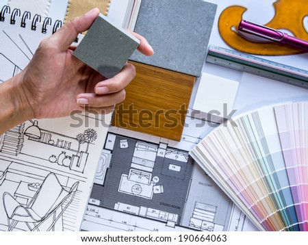 Interior designer's  hand working with illustration sketch,  material and color samples - stock photo