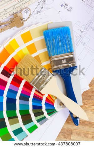 Interior designer's working desktop with architectural plan of the house, color palette and brushes - stock photo