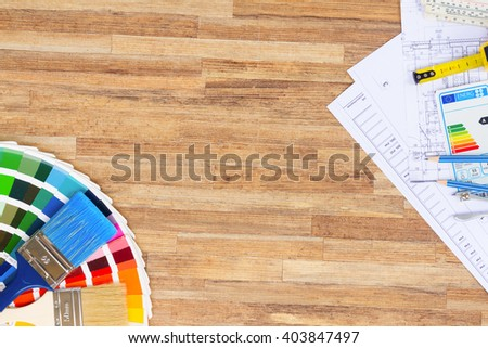 Interior designer's working table with  architectural plan of the house, color palette and  brushes, copy space on wooden table - stock photo