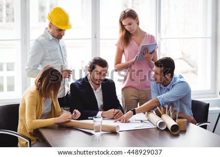 Interior designer with coworkers discussing blueprint during meeting - stock photo