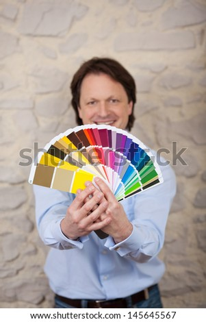 Interior designer with paint color cards in all shades of the rainbow held out in his hands - stock photo