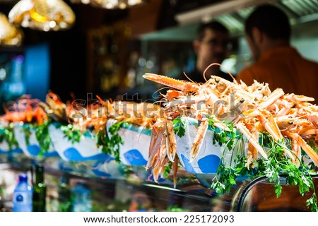 Interior of a busy fish market with detail on fresh scampi - stock photo
