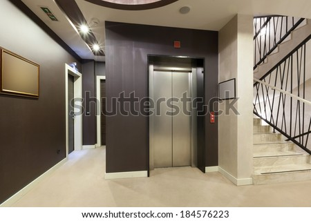 Interior of a corridor with passenger lift and marble stairs  - stock photo