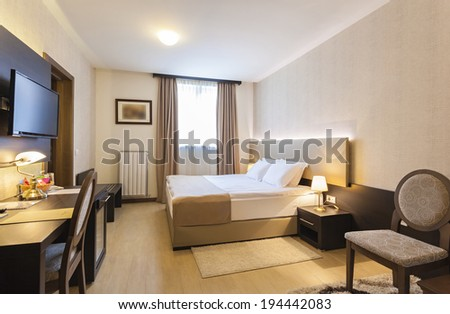 Interior of a hotel bedroom with framed wall mounted tv - stock photo