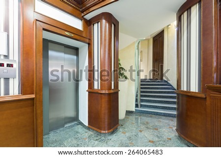 Interior of a hotel lobby with passenger lift and stairs - stock photo