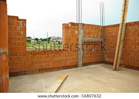 Interior of a house under construction with red brick walls - stock photo