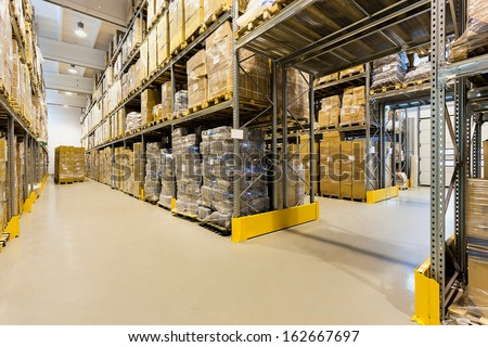 Interior of a huge spacious warehouse with carton boxes - stock photo